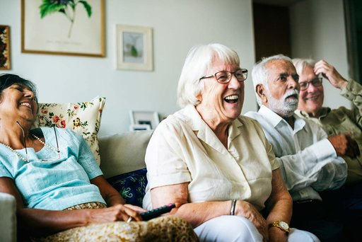 Elderly men and women sitting on a couch smiling